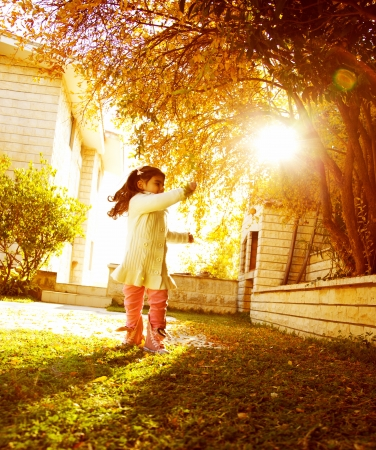 backyards: Image of happy small girl in sunny autumn day playing games in house garden, cheerful small female child run outdoors, sweet kid enjoying warm fall sunlight, carefree childhood