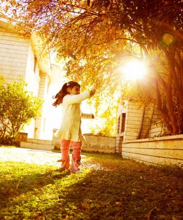 the yards: Imagen de ni�a feliz peque�o en d�a soleado de oto�o jugando en la casa de jard�n, alegres peque�os al aire libre femenino plazo ni�o, chico dulce disfrutando de la luz del sol caliente de oto�o, la infancia sin preocupaciones