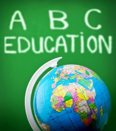 Photo of globe in classroom, handwriting alphabet on green chalkboard, elementary school, geography lesson, student study countries on map, knowledge and education concept, school supplies photo