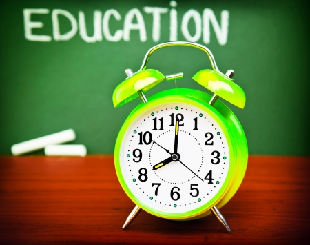 Photo of alarm clock on wooden desk in classroom, handwriting word education on green blackboard, autumn season, yellow watch in school class, back to school, knowledge concept  photo