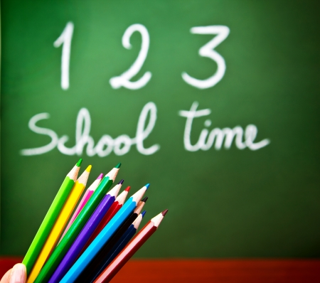 Image of colorful pencils and green chalkboard with selective focus, multi colors crayons in preschool, handwriting phrase school time on blackboard in classroom, education and knowledge concept photo