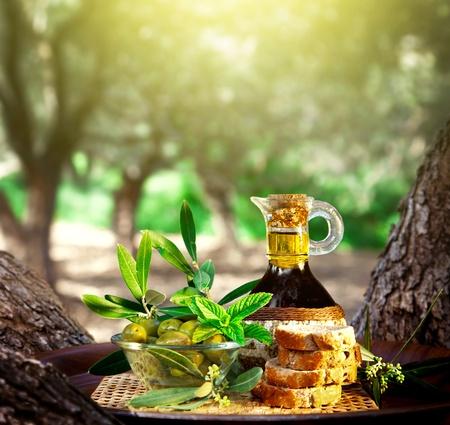 Foto de oliva naturaleza muerta, el aceite de oliva en botella y verde oliva en un tazón de vidrio con pan en bandeja al aire libre, la fruta fresca en el jardín a través de la puesta del sol, ensalada saludable vestidor, cocina mediterránea