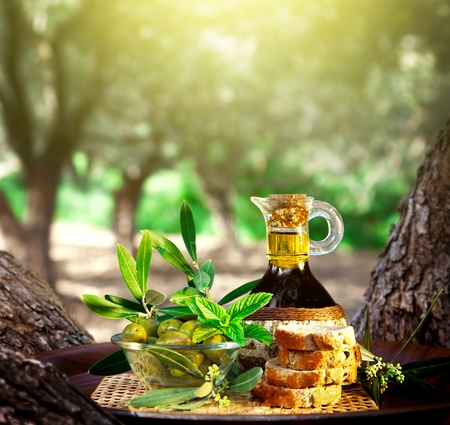 field mint: Photo of olive still life, olive oil in bottle and green olive in glass bowl with bread on tray outdoors, fresh fruit in garden over sunset, healthy salad dressing, mediterranean cuisine