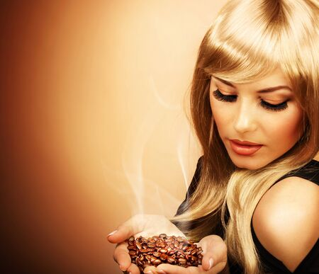 Closeup portrait of young beautiful lady holding hot roasted coffee beans, picture of attractive blonde girl enjoy coffee aroma, image of pretty elegant female isolated on brown background photo