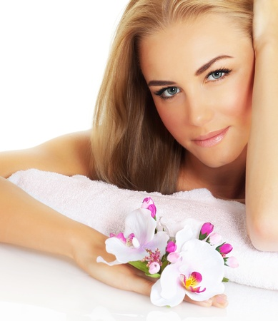 a beautiful woman with pink orchid isolated on white background, blonde pretty girl sitting and holding fresh flower in hand, young lady closeup portrait, day spa, beauty and health treatment photo
