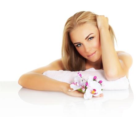 mujer desnuda sentada: Retrato de la mujer atractiva en el salón de spa, la imagen de la señora hermosa joven con el pelo rubio que sostiene rosa orquídea flor, linda chica con maquillaje natural, spa, salud y tratamientos de belleza, cuidado de la piel Foto de archivo