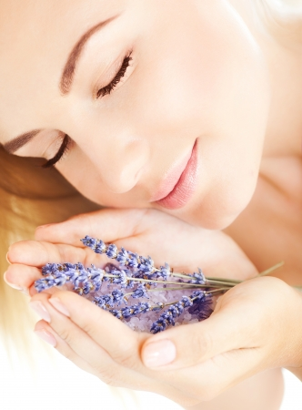 image of beautiful girl smell purple lavender flowers, closeup portrait of cute woman with closed eyes and holding sea salt and violet flower in hands, pretty female with clean skin, spa concept photo