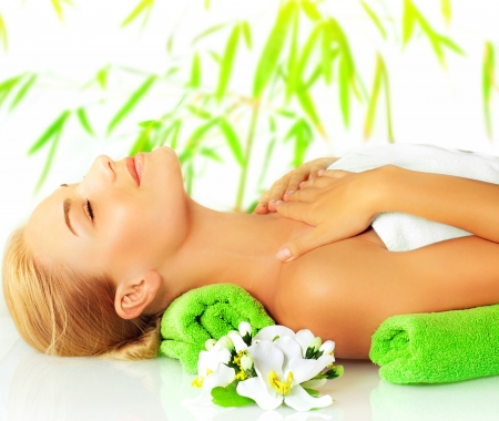 Closeup portrait of beautiful young lady in spa salon, attractive woman sleeping on massage table, side view of girl lying down with closed eyes enjoy dayspa, bamboo background and orchid flower photo