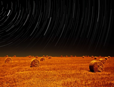 Picture of night landscape of farm field, starry sky above dry haystack on farmland, magic stars slow motion rotating above earth, autumn harvest season, starlight in night on cereal meadow    photo