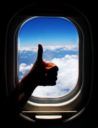 image of person arm with thumb up in the plane, blue sky with white clouds through airplane window frame, happy traveler, silhouette of tourist hand with gesture happiness over beautiful skyline