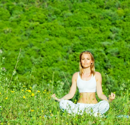 lotus pose: Photo of beautiful woman doing yoga exercise outdoors, mental health, healthy lifestyle, cute young lady sitting in lotus pose, pretty girl is engaged in fitness in park over green tree background  Stock Photo
