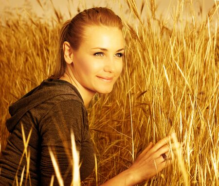 Image of pretty woman sitting on wheat field, sexy blond model relaxed and dreaming in countryside, closeup portrait of cute young lady on golden ryes background, autumn harvest season photo