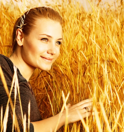 an attractive smiling girl sitting in golden wheat field, closeup portrait of beautiful young blond female on yellow hay ryes background, grain harvest season, conceptual of autumn season  photo