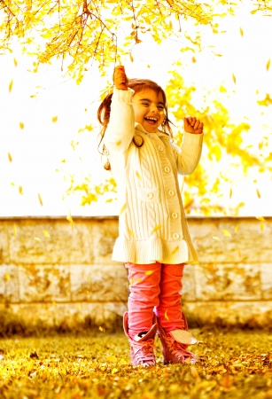 a cute happy small girl standing in autumn park, cheerful sweet female child wearing colorful warm clothes and playing outdoor with old dry yellow trees leaves, fall season photo