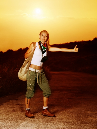 Image of active sporty girl traveling hitchhike, blond woman on road waiting for car, tourist female standing on highway with raised hand and stop auto, conceptual of vacation, adventure  photo