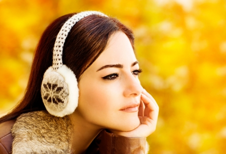 Photo of beautiful woman wearing clothing for head, closeup portrait of attractive arabic female on golden autumn background, pretty young brunette lady in warm earmuff, fall season concept