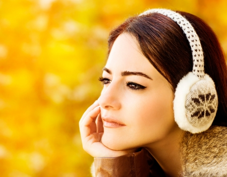 muff: Image of beautiful woman on autumn background, closeup portrait of gorgeous arabic female, brunette girl wearing warm ear muff, cute young lady wear autumnal clothing accessories, fall season