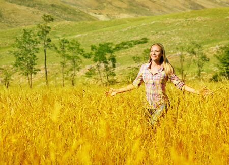 a pretty woman running on golden wheat field, beautiful young lady having fun outdoors, happy smiling girl enjoying freedom on crop meadow, grain harvest season, autumn landscape  photo