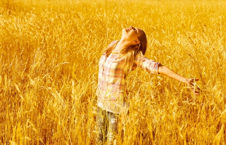 arm raised: a beautiful woman standing on wheat field, pretty teen girl stand on golden rye land with raised open hands and looking up, carefree young girl enjoying freedom outdoors, harvest season