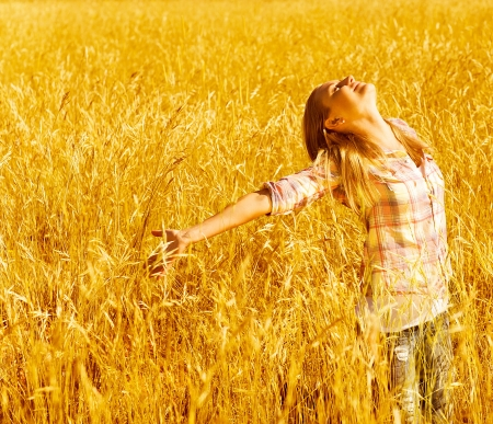 woman arms up: Picture of cheerful teenager having fun in countryside, cute happy female standing on wheat field with raised open hands and looking up, blond girl enjoying autumn nature, fall season Stock Photo