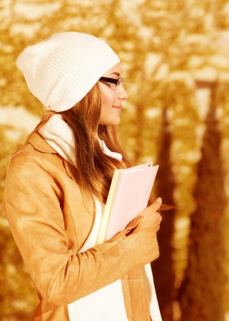 a pretty student girl standing in autumn park and wearing beige leather coat with white warm hat, cute schoolgirl holding book, side view of beautiful teenager, back to school photo