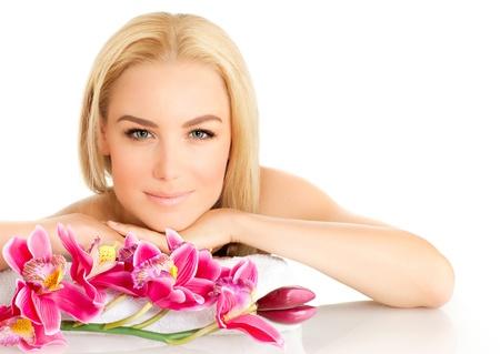 Afbeelding van gelukkig mooie volwassen meisje in spa salon, aantrekkelijke blonde vrouw genieten van dayspa, mooie vrouw geïsoleerd op witte achtergrond met roze orchidee bloemen, gezonde levensstijl, zen en spa concept van