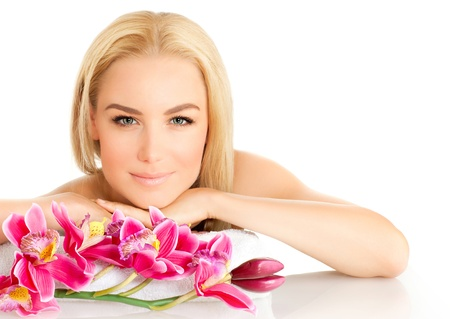 Image of happy beautiful adult girl in spa salon, attractive blonde female enjoying dayspa, pretty woman isolated on white background with pink orchid flowers, healthy lifestyle, zen and spa concept  photo