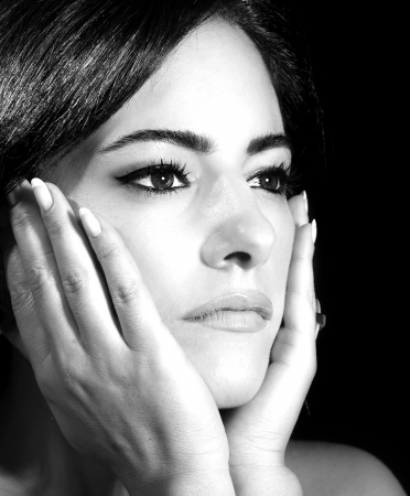 Black and white photo of attractive female touching her face, closeup portrait of brunette arabic female with perfect stylish makeup, gorgeous glamorous young lady, luxury beauty salon photo