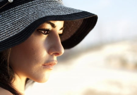 woman profile face: Image of attractive arabic female wearing black beach hat, closeup portrait of stylish elegant woman, beautiful girl isolated on blur background, side view of luxury glamorous young lady