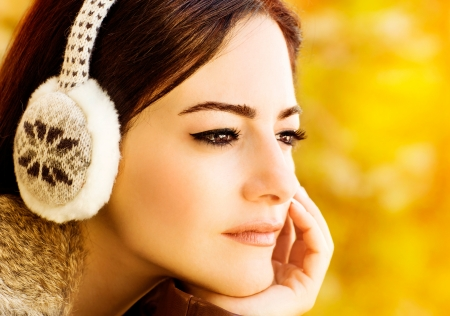 earmuff: Photo of pretty woman, closeup portrait of brunet arabic girl with fashionable makeup wearing warm earmuff isolated on blur autumn background, gorgeous female waiting for someone, fall season