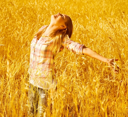 Image of pretty young woman enjoying autumn rural nature, active teen girl standing on golden dry wheat field with raised open hands and looking up, grain harvest concept, fall season photo