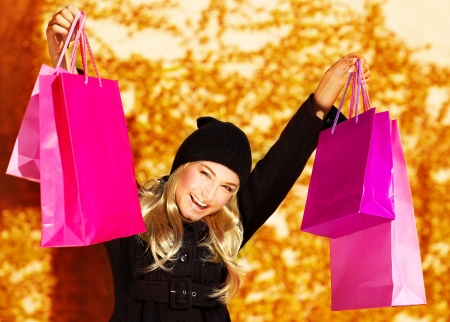 bag of money: Image of happy cute girl with pink shopping bag, cheerful young lady holding paper presents bags in fall park, smiling blond woman raised up hands over golden autumn background, spending money concept