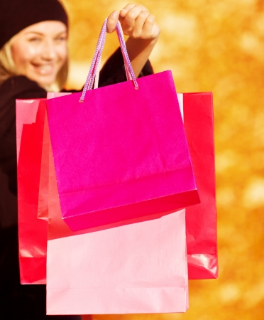 gift spending: Photo of happy female holding pink shopping bag isolated on yellow autumnal background, smiling buyer girl enjoying of her purchase, autumn seasonal sale, spending money concept