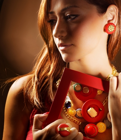 jewelry design: Photo of beautiful fashionable woman isolated on brown background, close up portrait of gorgeous female with red frame, pretty girl wearing stylish luxury jewelry, beauty and fashion concept