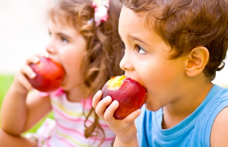 kids eating healthy: Photo of two happy children eating apples, brother and sister having picnic outdoors, cheerful kids biting red ripe peach, adorable infant holding fresh fruits in hands, healthy nutrition concept  Stock Photo