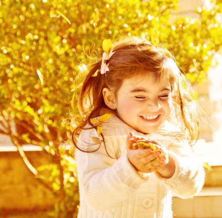 Photo of pretty happy little girl enjoying autumn nature in park, cute cheerful child playing with golden leaves in dry forest, brunette small baby girl with closed eyes laughing in fall sunny day photo