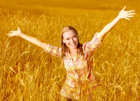 Picture of happy cheerful girl having fun on wheat field, beautiful blond woman with raised up hands enjoying freedom outdoors, agriculture lifestyle, autumn harvest concept, fall season photo