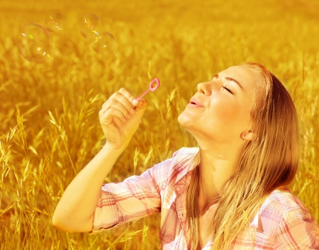 Image of cute blond girl blowing soap bubbles on wheat field, happy teenager having fun on golden crop meadow, closeup portrait of pretty young woman playing game on farm land, autumn season photo