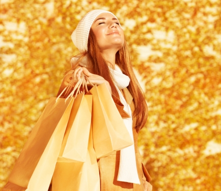 Photo of pretty happy woman with shopping bags in park, smiling cute blond girl enjoying of new purchase over autumn foliage background, fashion and style lifestyle, spending money concept