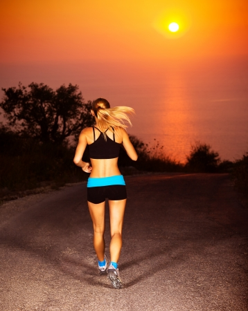 Picture of sporty blond female running along the road over sunset, beautiful active woman doing fitness exercise outdoors, rear view of healthy jogger girl wearing sports clothes, healthy lifestyle photo