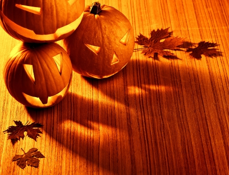 Picture of halloween glowing pumpkins border, three orange carved pumpkins and old dry leaves on wooden background, scary holiday shadow, traditional halloween decoration, jack-o-lantern Foto de archivo