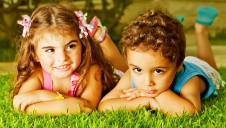 Picture of two happy kids laying down on fresh green grass, brother and sister enjoying summer holiday, cute girl and pretty boy having fun outdoors, happy friends playing on backyard  photo