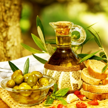 arabic food: Photo of olive oil still life, healthy organic salad dressing, lebanese cuisine, glass bottle with olive oil, marinated olives and bread on tray in garden, homemade food, harvest season  Stock Photo