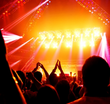 music concert: Image of rock concert, active people enjoying party, cheerful teens applauding to musician band, famous dj on the stage, new year celebration, night lifestyle,  dancing nightclub, music festival   Stock Photo