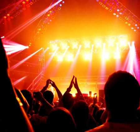 concierto rock: Imagen de un concierto de rock, las personas activas disfrutando partido, los adolescentes alegres que aplauden a la banda de m�sicos, dj famoso en el escenario, celebraci�n del A�o Nuevo, estilo de vida nocturno, discoteca bailando, festival de m�sica Foto de archivo