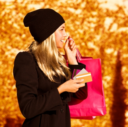 a cute blond girl with pink shopping bag, side view of pretty woman holding paper present bag, beautiful happy shopper over autumn yellow foliage background, seasons sales   photo