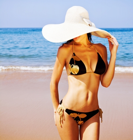 Picture of perfect female on sea coast, young sexy lady in white stylish hat on the beach, seductive woman wear fashionable black swimwear, tanning girl near ocean, tropical resort, summer holiday   photo