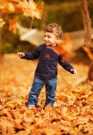 a cute little boy enjoying autumnal nature, pretty infant playing in park, cheerful baby boy having fun outdoors, adorable kid in fall forest, happy child play with dry orange maple leaves   photo