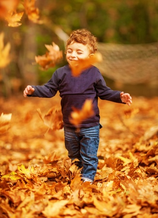 Picture of pretty baby boy running in autumnal park, little child playing with old dry trees foliage, adorable toddler play game on backyard, enjoying walk, beauty autumn season, happy childhood    photo