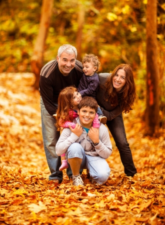 fall fun: Picture of lovely family in autumn park, young parents with nice adorable kids playing outdoors, five cheerful person have fun on backyard in fall, happy family enjoy autumnal nature